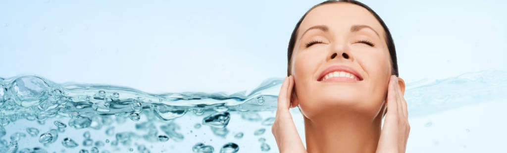 beauty, people, skincare, moisturizing and health concept - smiling young woman cleaning her face over water